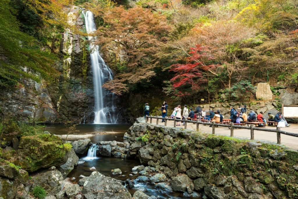 People taking photos at the hidden and beatuiful waterfall in Minoo Park.