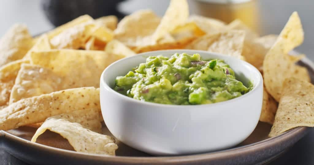 Plate of corn chips and Guacamole.