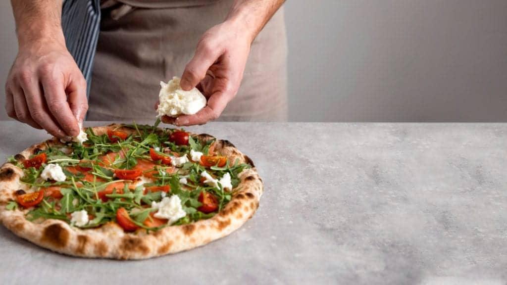 Man putting mozzarella on baked pizza dough with smoked salmon slices