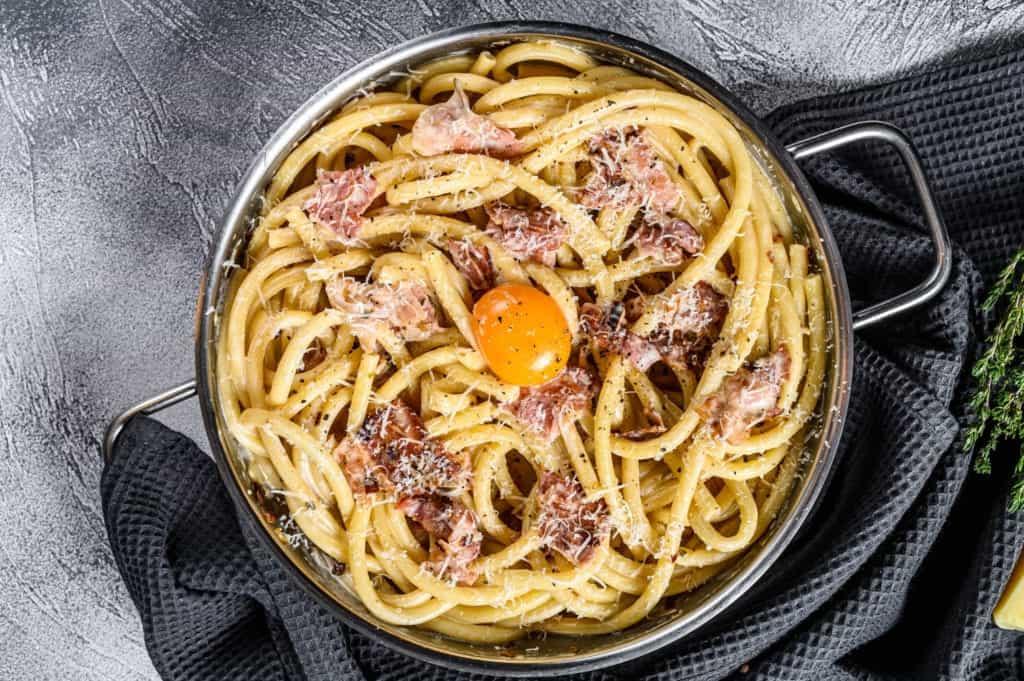 Plate and skillet och pasta carbonara.