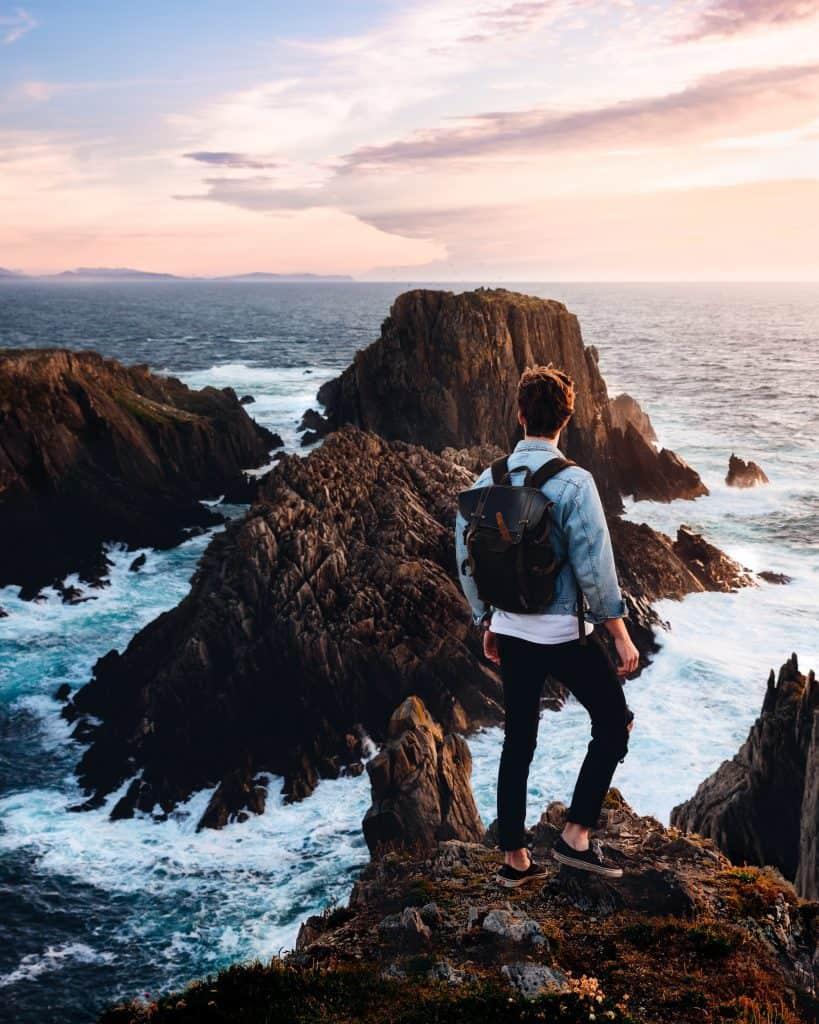 En yngre man står på en kant och tittar ut över havet.