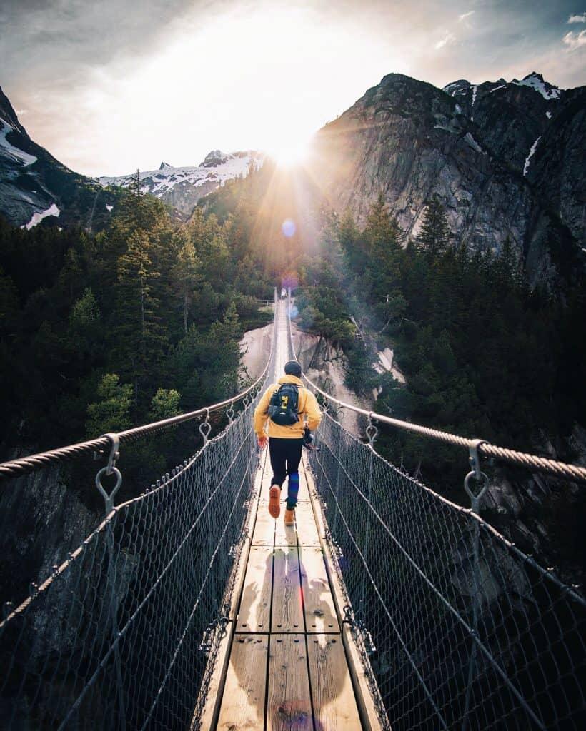 En man i gul jacka vandrar på en repbro i skogen.