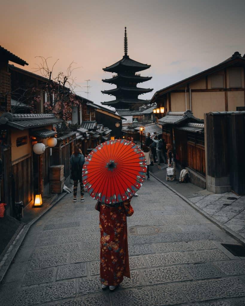 Kvinna i kimono vandrar mot en Pagoda.